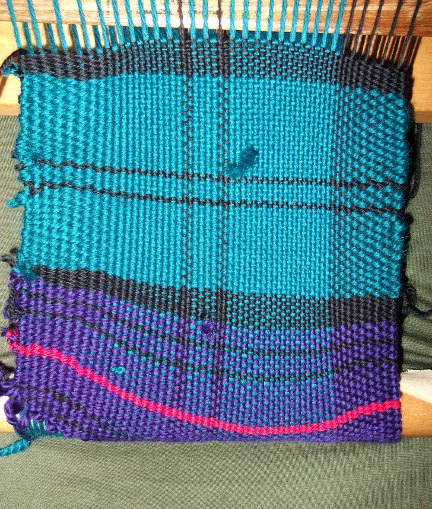 Purple and green with black and red accents.  My loom is only wide enough to do half the warping pattern at a time, but I'll get there eventually. :-D