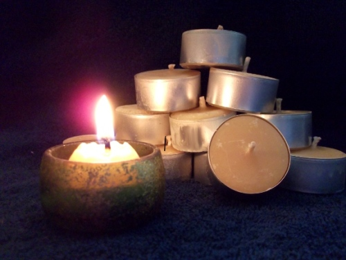 A stack of eleven beeswax tealights, with one tealight lit and burning in the foreground (in a small dark green and gold-flecked holder).