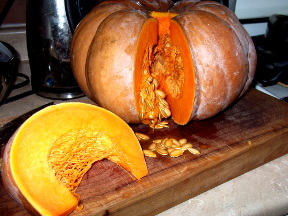Huge, ripe fairy tale pumpkin - light brown skin, deep orange flesh, and lots of seeds - sitting on on a thick butcher's block cutting board. The pumpkin has a big wedge cut out of it, so you can see how thick the flesh is. Photo by me, taken last January.