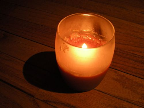 A lit tealight in a glass holder casting a shadow onto a wooden floor. Courtesy of Wiki Free Images.