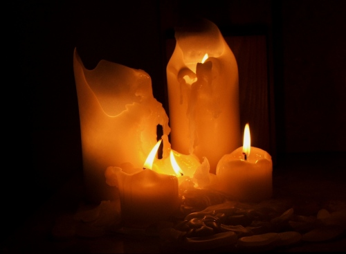 Two tall (pillar) and three short (votive) candles, that have been burning, for some time, in a dark place. - Photo is public domain courtesy of wiki free images.