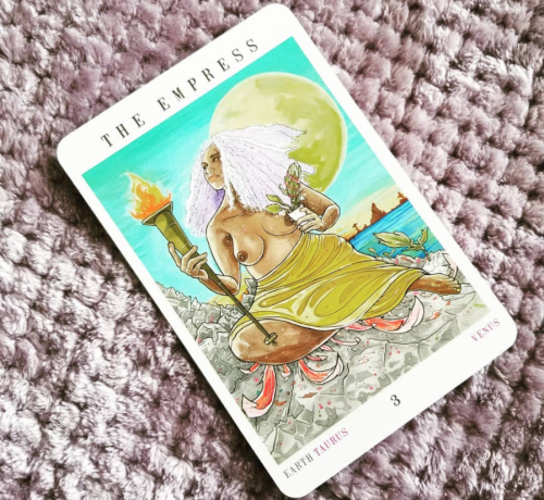 Next World Tarot - The Empress - A Black femme w/ lavender hair and a yellow skirt, carries a torch and holds a potted plant. A huge, full moon rises in the background.