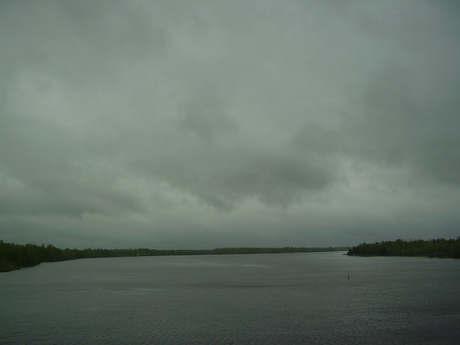A grey sky full of heavy clouds hangs over the equally grey Rideau River. Photo by Leslie Mateus, via Wiki Free Images