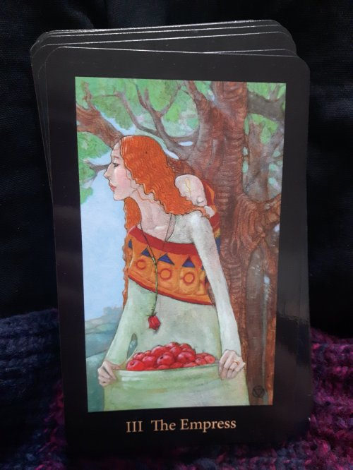 The Empress - Mary El Tarot - A red-haired person in a long green dress, with a baby tied to their back, stands under a mature tree, holding a basket of fruit