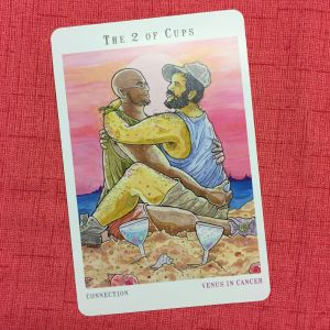Two of Cups - Cristy C Road - Next World Tarot - Two sweeties embrace on a beach, clearly besotted with one another