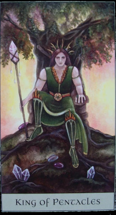 Crystal Visions Tarot - King of Pentalces - A woman with long, brown hair and an antler crown, green greeves, and a staff topped with a big crystal, sits enthroned under a spreading oak. Crystal points poke out of the ground at her feet.